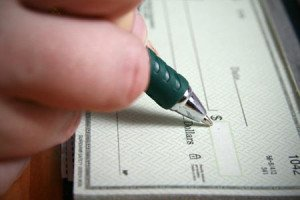 Person signing check in checkbook