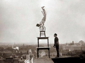 Man Balancing on Chair on Top of Building