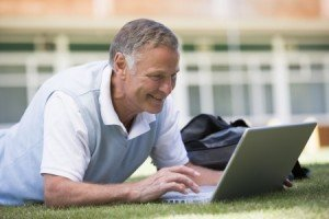 Baby Boomer Man Laying in Grass Looking at Laptop