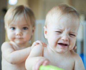 Upset Baby Being Consoled by Another Baby
