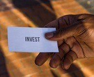 Hand Giving Out Card that Says Invest