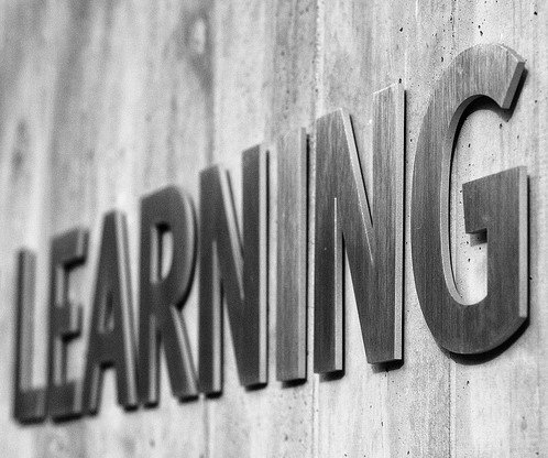 Learning Sign in Silver Letters on Concrete Wall