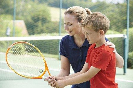 Female Tennis Coach Coaching a Young Boy