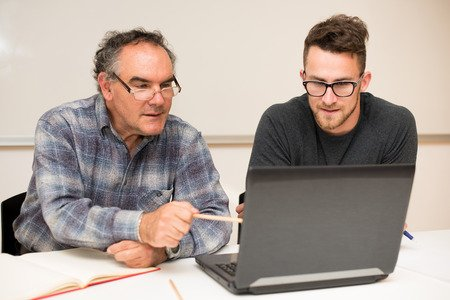 Young man teaching older to use computer