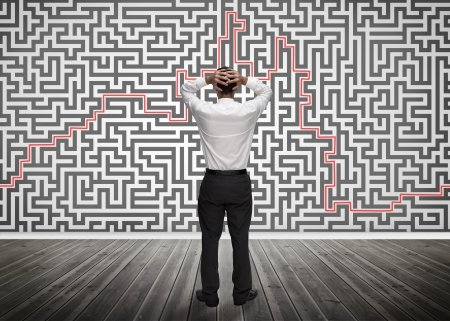 Confused Businessman Looking at a Maze on a Wall