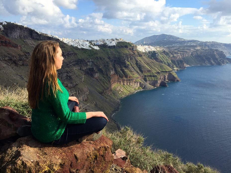 Young Woman Meditating on a Cliff